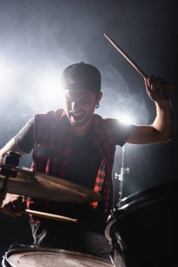Rock band drummer holding drumstick and playing drums with back light and smoke on background stock vector