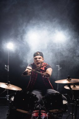 Screaming drummer with crossed drumsticks looking at camera, while sitting at drum kit with smoke and backlit on background stock vector