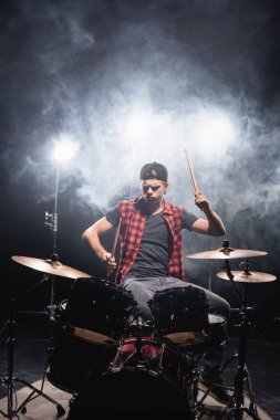 Serious musician with drumsticks playing drums with smoke and backlit on black stock vector