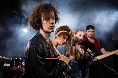 KYIV, UKRAINE - AUGUST 25, 2020: Curly musician with drumsticks looking at camera with smoke and blurred members of rock band on background stock vector