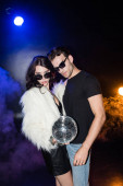 Curly woman holding disco ball, while touching boyfriend shirt and looking at camera with smoke and backlit on black
