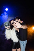 Man closing camera with hand, while embracing woman holding disco ball with backlit and smoke on black