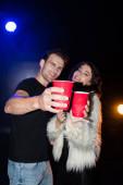 Šťastný pár drží červené plastové poháry a dívá se na kameru s podsvícením na černé, na rozmazaném pozadí