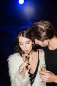 Man in shirt looking at seductive brunette woman with glass of champagne with backlit on black