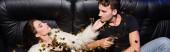 Muž se dívá na vášnivou ženu se sklenkou šampaňského ležící na pohovce, zatímco konfety padají v nočním klubu, prapor