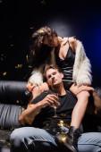 Sexy Freundin mit einem Glas Champagner sitzt auf dem Sofa hinter einem ernsten Mann und schaut in die Kamera, während Konfetti im Nachtclub fällt