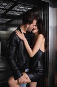 Mann in Lederjacke küsst und hält Bein der verführerischen Frau in schwarzem Kleid im Fahrstuhl