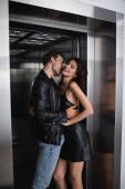 Mann in Lederjacke umarmt lächelnde Frau mit geschlossenen Augen im Fahrstuhl