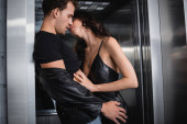 Seductive woman in leather dress undressing man touching hip in elevator