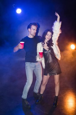 Smiling brunette woman with hand in air standing near boyfriend with plastic cup with smoke and backlit on black