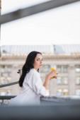 side view of brunette woman drinking orange juice