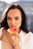 Porträt einer brünetten Frau in beiger Unterwäsche und weißem Hemd, die Wassermelone isst