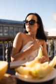 sexy brünette Frau mit Sonnenbrille und weißem Laken, die Melone auf dem Balkon isst