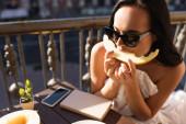 Brünette Frau mit Sonnenbrille und weißem Laken isst Melone auf Balkon