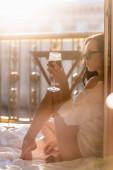 bruneta žena v slunečních brýlích a bílé košili pití vína na balkóně