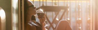 Brunette woman in sunglasses drinking wine on balcony, horizontal banner stock vector