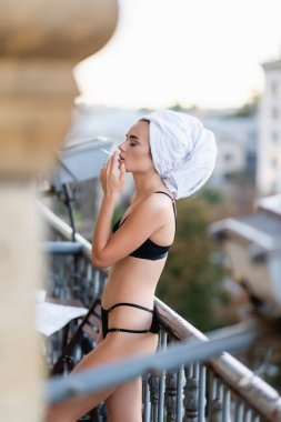 Sexy young woman in black underwear with towel on head smoking cigarette on balcony stock vector