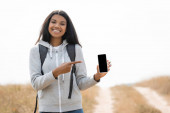 Smiling african american treveller pointing with finger at smartphone with blank screen near path on blurred background