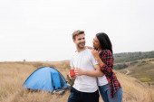 Smiling african american woman hugging boyfriend with cup near tent on blurred background outdoors