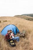 Usmívající se mezirasový pár s dekou a pohár sedí v blízkosti stanu na travnatém trávníku