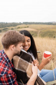 Man hugging smiling african american woman in blanket with cup on grassy meadow