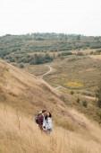 Usmívající se interracial pár s batohy stojící na kopci s krajinou na pozadí