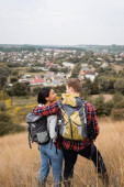 Photo Back view of tourist with backpack hugging smiling african american girlfriend on grassy hill