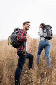 Photo Smiling man holding backpack while standing near african american girlfriend on hill with grass