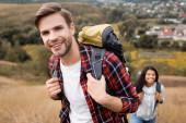Turistický úsměv na kameru při chůzi v blízkosti africké americké ženy na rozmazaném pozadí venku