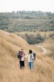 Interracial couple with backpacks holding hands on grassy hill during trip