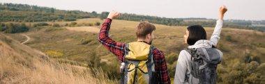 Smiling african american hiker showing yeah gesture near boyfriend outdoors, banner stock vector