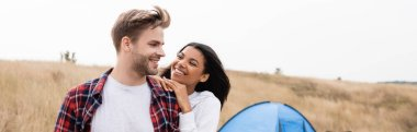 Smiling man looking at african american girlfriend with tent and field on blurred background, banner stock vector