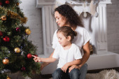 Matka a dcera dotýkají vánoční míč na slavnostní borovice v blízkosti krbu