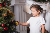 Lány áll kandalló mellett, és megérinti karácsonyi labda ünnepi fenyő otthon