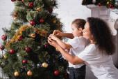 Boční pohled na maminku a dceru zdobení vánoční borovice u krbu doma