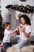 Lányom és anyám karácsonyi labdák közelében díszített fenyő és kandalló
