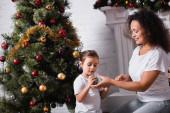 Mutter und Tochter sitzen mit Weihnachtskugeln neben geschmückter Kiefer zu Hause