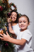 Selective focus of girl touching christmas balls on pine near mother at home