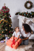 Mother and daughter looking at each other near gift boxes at home
