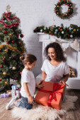Mother with daughter touching big gift box near fireplace and pine at home