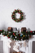 Photo Christmas wreath above fireplace decorated with christmas balls and stockings