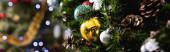Panoramatický záběr zdobeného smrku s vánočními míčky a šiškami