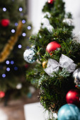Selective focus of pine branch decorated with christmas balls and bow