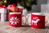 Selektiver Fokus von Tassen mit gestrickten Weihnachtsständern auf Holztisch
