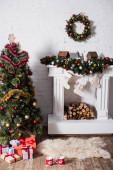 Dárkové boxy v blízkosti slavnostní borovice a vánoční věnec nad zdobeným krbem