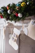 Kandalló díszített karácsonyi harisnya, fenyő ágak és karácsonyi labdák