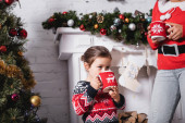 Photo Little girl drinking from cup, standing with mother near fireplace at home