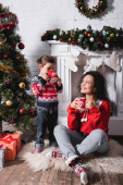 Mother sitting on rug near daughter drinking from cup near festive pine at home