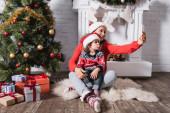 Matka a dcera v Santa klobouky přičemž selfie v blízkosti zdobené borovice doma