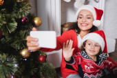 Mother and daughter with waving hand taking selfie near decorated pine
